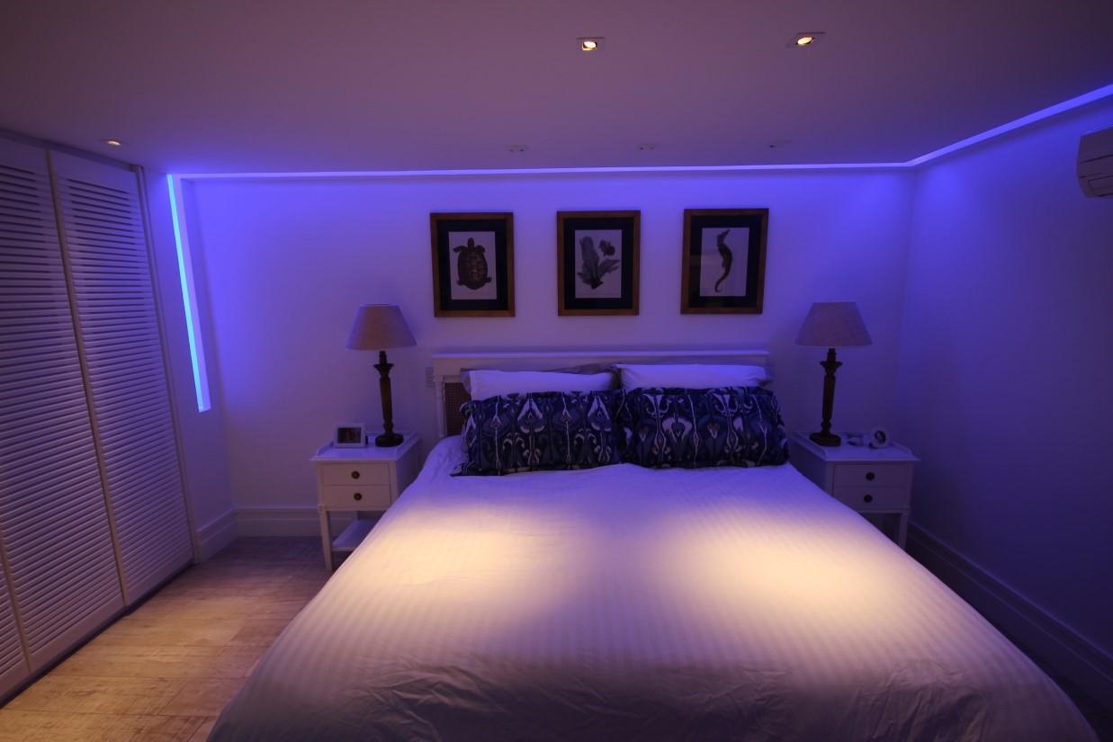 Iluminação com efeito roxo para o quarto de casal